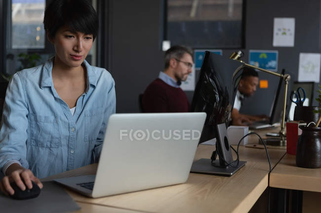 Attentive colleagues working with computers at desk in office. — Stock Photo