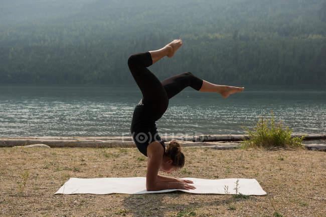 Fit femme faire du yoga acrobatique près de la côte par une journée ensoleillée — Photo de stock