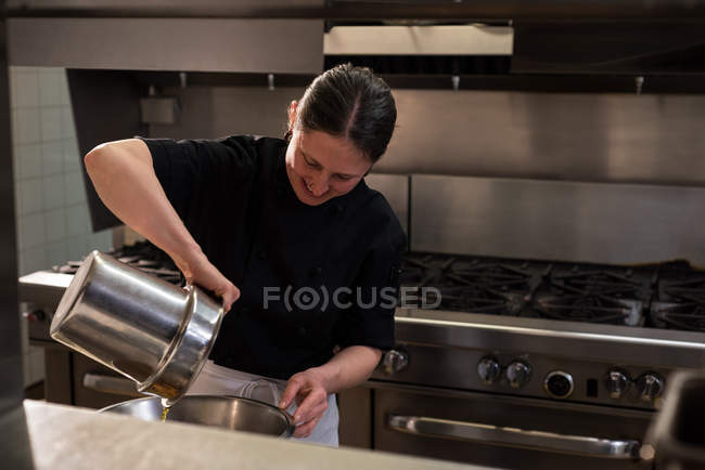 Chef pouring oil into a container in commercial kitchen — Stock Photo