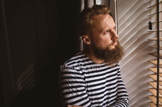 Close-up de homem pensativo olhando para fora da janela — Fotografia de Stock