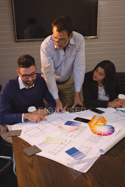 Business people discussing blueprints and graph chart in office. — Stock Photo