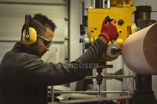 Männlicher Arbeiter, der eine Maschine in der Fabrik bedient — Stockfoto