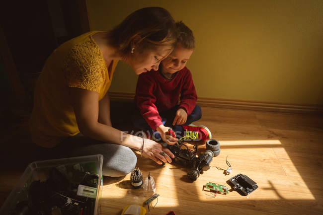Mother and son repairing toy car in bedroom at home — Stock Photo