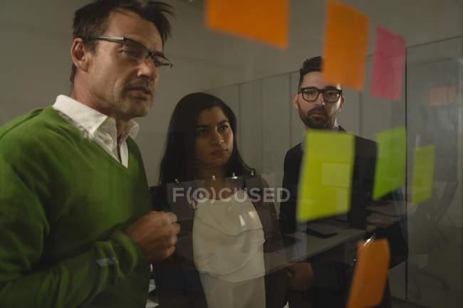 Gli uomini d'affari discutono su appunti appiccicosi al muro dell'ufficio . — Foto stock