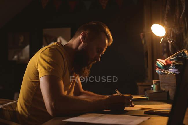 Человек, сидящий на стуле и пишущий письмо дома — стоковое фото