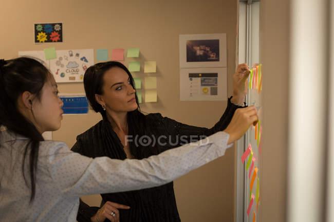 Mujeres colegas de negocios discutiendo sobre notas adhesivas en la oficina - foto de stock