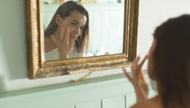 Aplicar o creme de cara na frente do espelho, em casa de mulher. — Fotografia de Stock