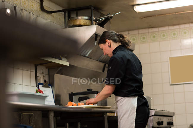 Concentrated chef chopping vegetables in the commercial kitchen — Stock Photo