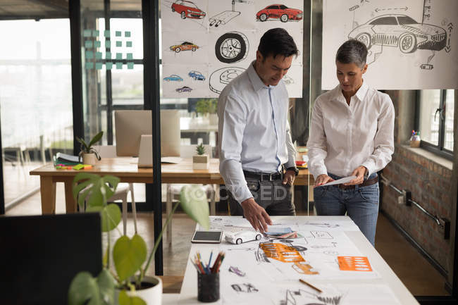 Business colleagues discussing over sketches in office. — Stock Photo
