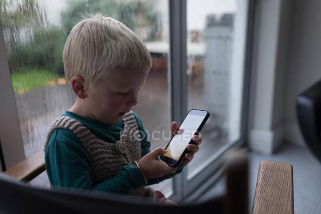 Мальчик использует мобильный телефон, сидя на стуле дома . — стоковое фото