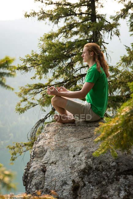 S'adapter homme assis en position de méditation sur le bord d'un rocher au moment de l'aube — Photo de stock