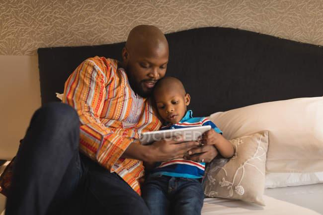 Батько і син, використовуючи цифровий планшетний в спальні в домашніх умовах. — стокове фото