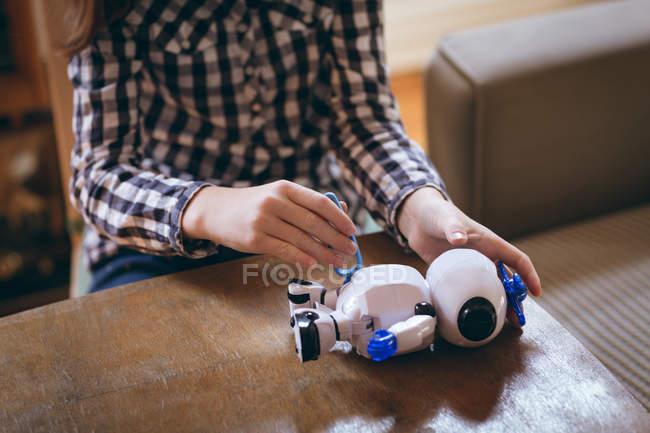 Imagen recortada de niña juguete robótico de fijación en el hogar - foto de stock
