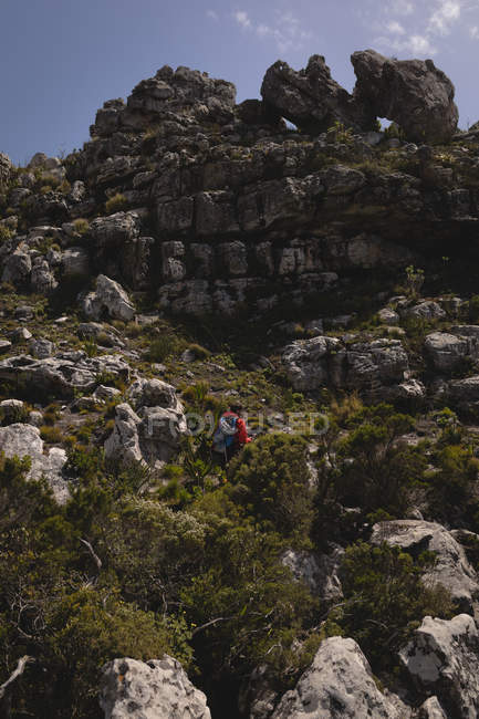 Hiker climbing up hill  with backpack on a sunny day — Stock Photo