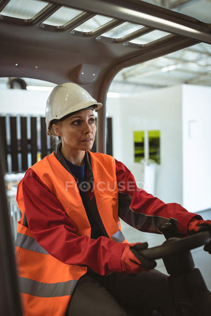 Female worker driving forklift in the warehouse — Stock Photo
