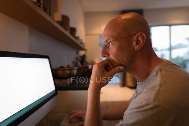 Man working on personal computer at home, side view. — Stock Photo
