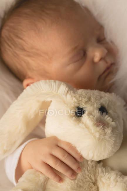 Bebê recém-nascido dormindo com brinquedo de pelúcia coelho. — Fotografia de Stock
