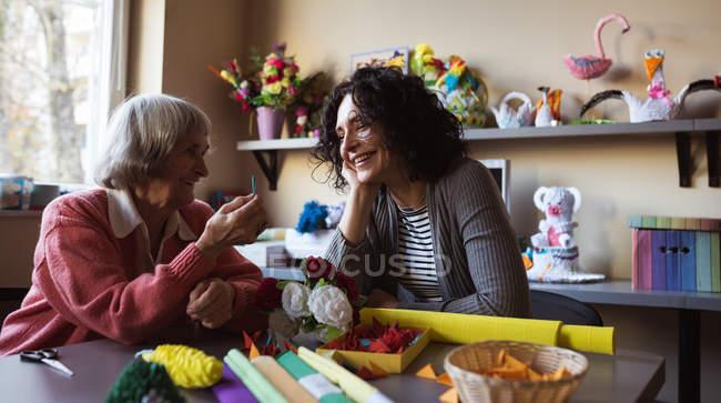Улыбаясь старший женщина, взаимодействующих с сторожа в доме престарелых — стоковое фото