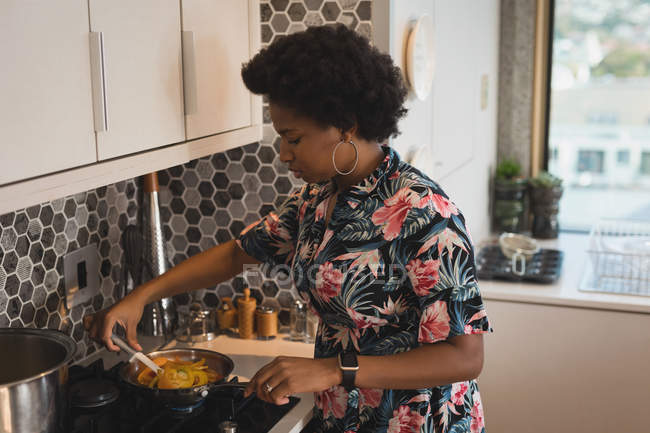 Woman preparing food in pan on stove in kitchen. — Stock Photo