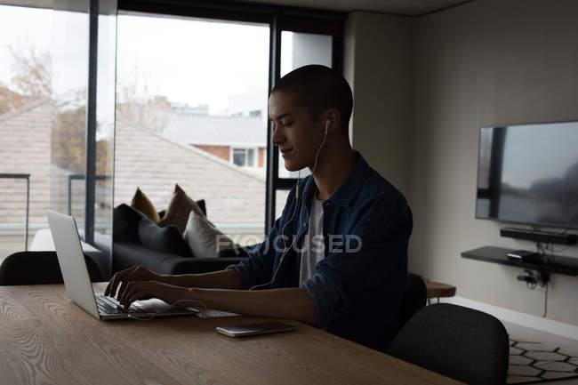 Young man listening music while using laptop at home — Stock Photo