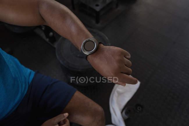 Gros plan sur smartwatch poignet masculin dans le studio de remise en forme. — Photo de stock