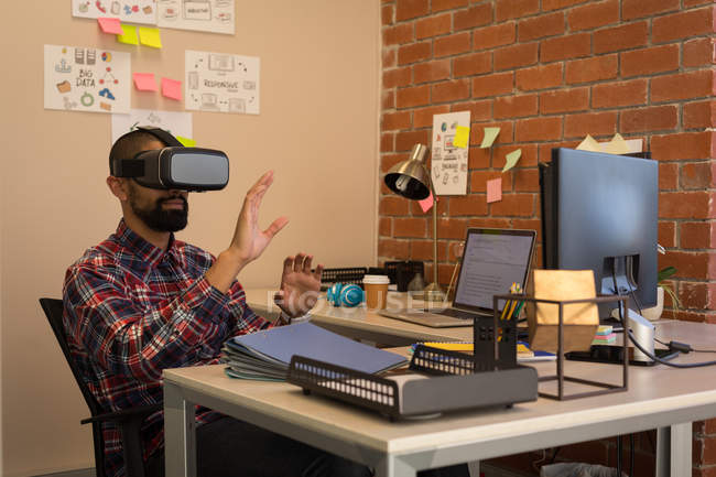 Male executive using virtual reality headset at desk in office — Stock Photo
