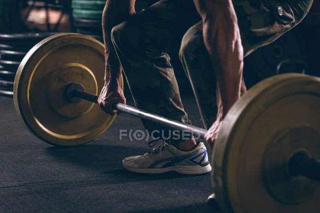 Low section of muscular man exercising with barbell in the fitness studio — Stock Photo