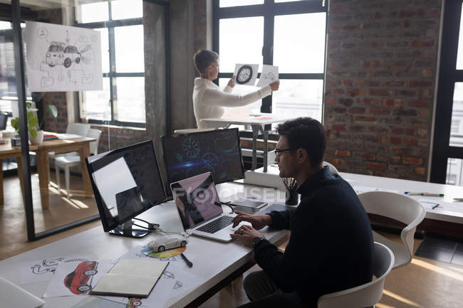 Businessman using laptop while colleague looking at sketch in office. — Stock Photo