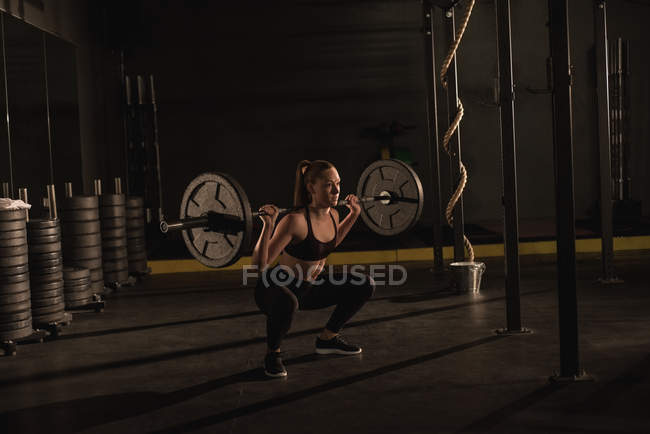 Young woman lifting with barbell in gym — Stock Photo