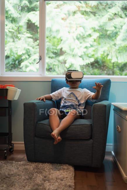 Мальчик использует гарнитуру виртуальной реальности в гостиной дома — стоковое фото