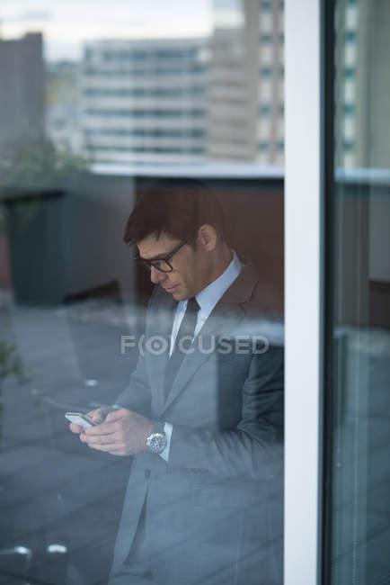 Geschäftsmann benutzte Handy in der Nähe von Glasfenster — Stockfoto