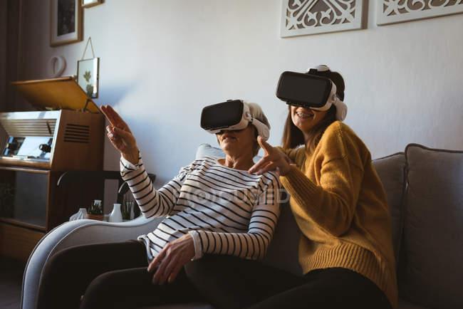 Старші жінки і дочка носити гарнітуру віртуальної реальності, відпочиваючи на диван — стокове фото