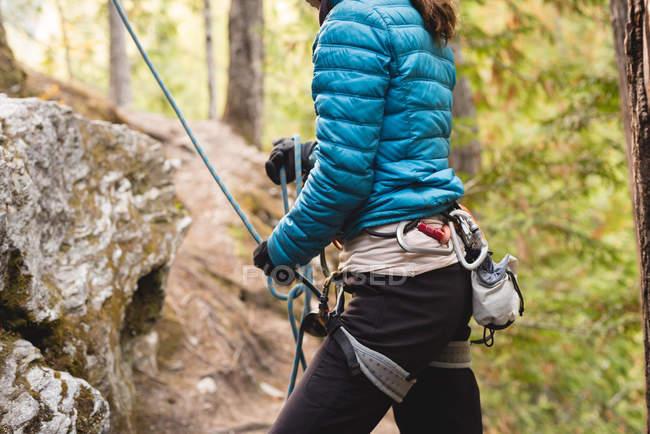 Partie médiane de l'alpiniste se préparant à escalader la falaise — Photo de stock