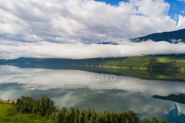 Beautiful view of white clouds reflecting in the river amidst green landscape — Stock Photo