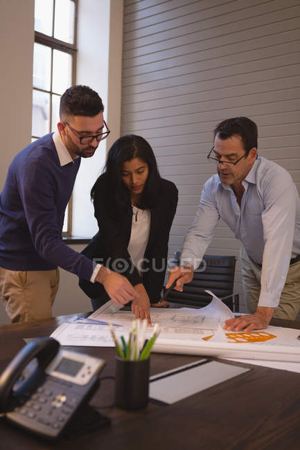 Business colleagues discussing over blueprints in meeting room at office. — Stock Photo