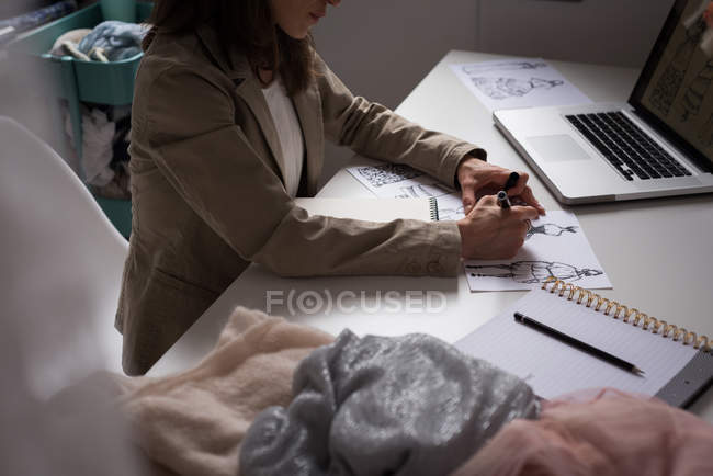 Mid section of fashion designer making sketches in design studio. — Stock Photo