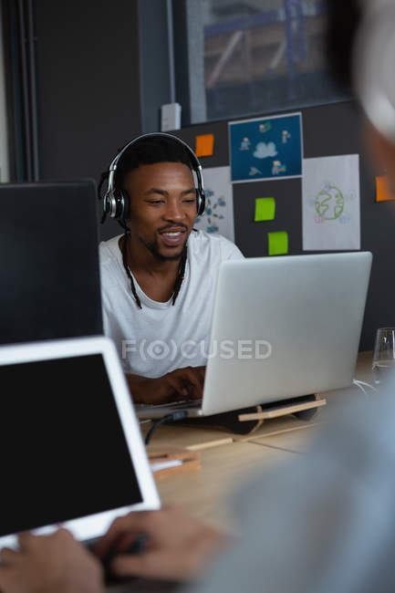 Smiling executive working at laptop on desk in office. — Stock Photo