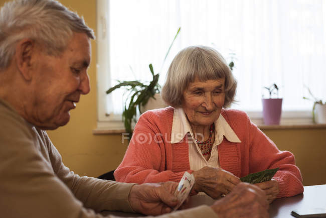 Senior friends playing cards at nursing room — Stock Photo