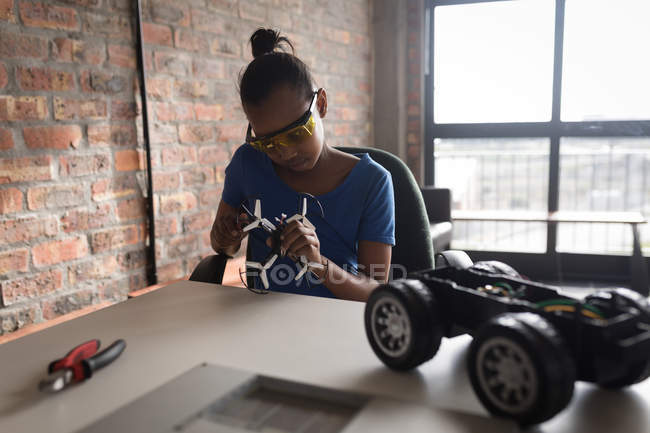 Girl repairing drone and electric model car in office. — Stock Photo
