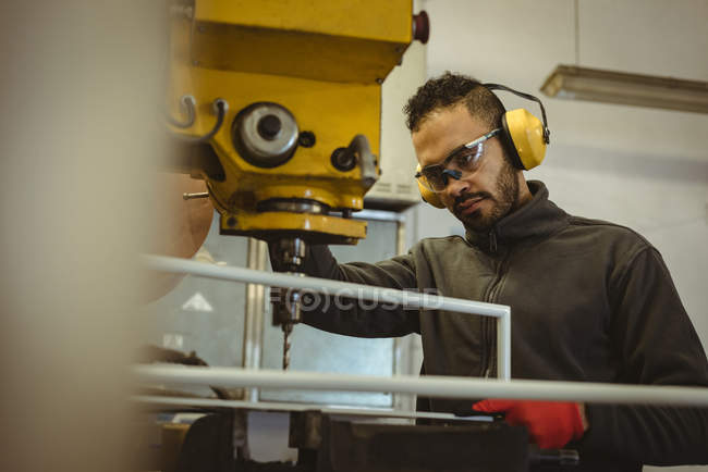 Male worker operating a machine in the factory — Stock Photo