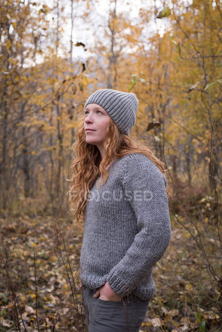 Beautiful woman in warm clothing standing in the autumn forest — Stock Photo