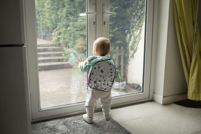 Реальный вид девочки со школьной сумкой, выглядывающей через дверь — стоковое фото