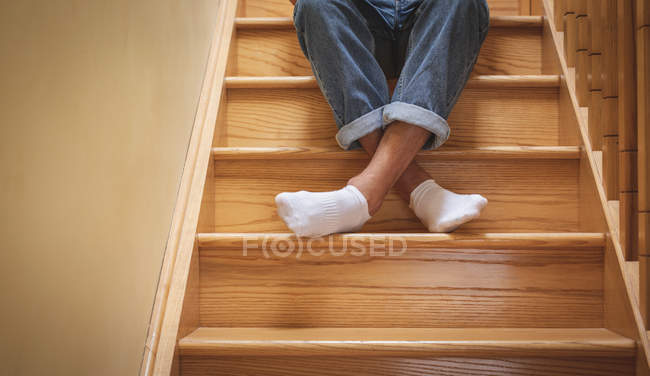 Low section of man sitting on staircase at home. — Stock Photo