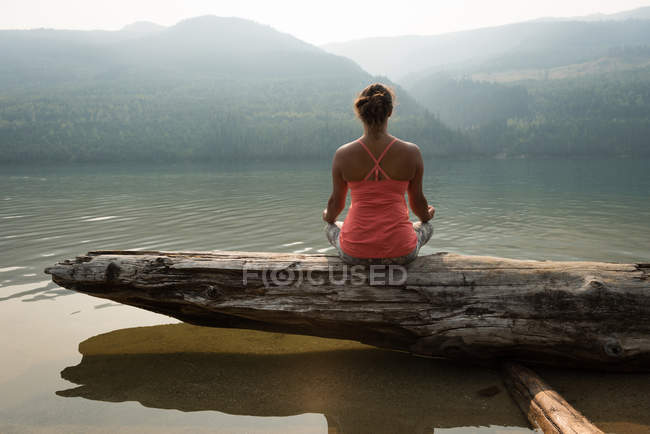 Fit woman sitting in meditating posture on a fallen tree trunk on a sunny day — Stock Photo