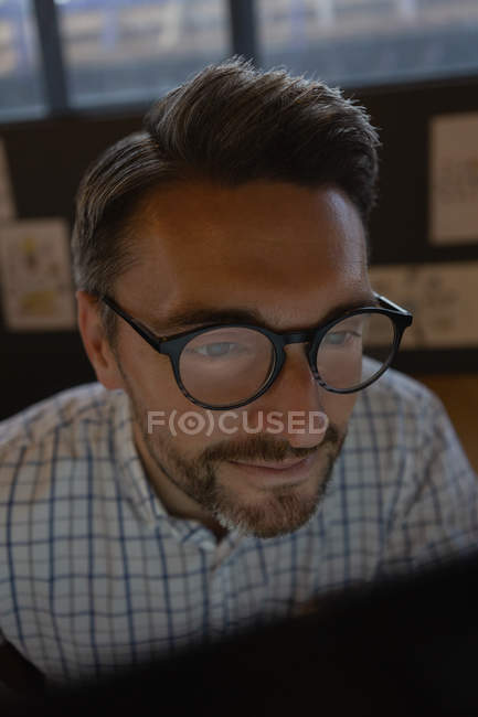 Close-up of male executive in glasses working by computer in office. — Stock Photo