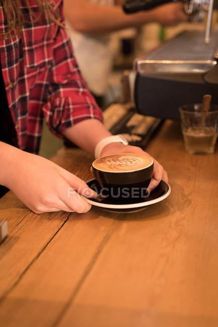 Mittleren Bereich der weiblichen Barista Kaffee am Schalter im Café serviert — Stockfoto