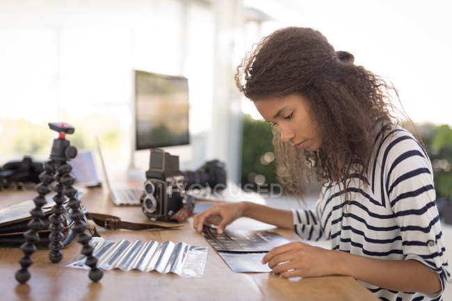 Beautiful photographer working at desk in the photo studio — Stock Photo