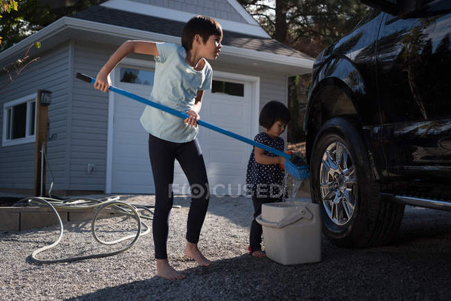 Siblings washing car together outside garage on a sunny day — Stock Photo