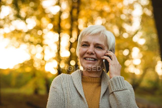 Gros plan d'une femme âgée souriante parlant au téléphone dans un parc d'automne — Photo de stock