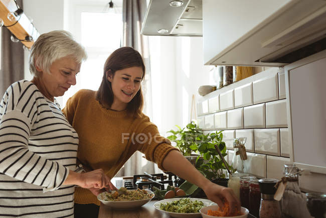 Senior woman and daughter cooking together in the kitchen at home — Stock Photo
